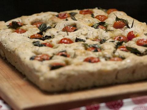 Focaccia con tomate y hierbas sobre plancha de madera